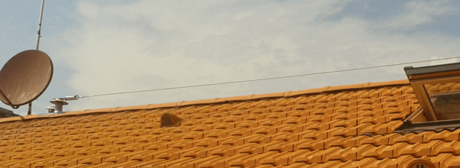 antenna parabolica e finestra aperta sul tetto di una casa
