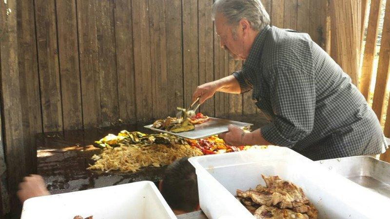 uomo prende cibo da una griglia