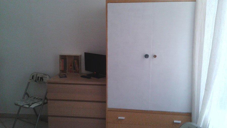 una stanza con un armadio bianco e accanto un mobile marrone con un cassetto e sopra una tv