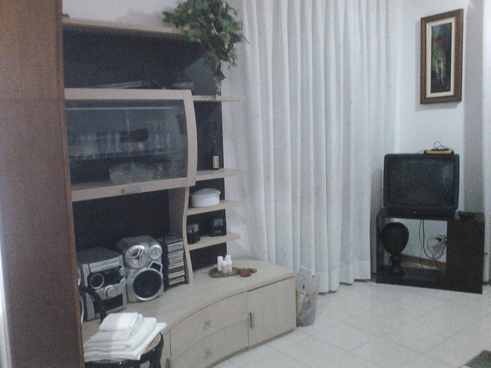un salotto con un mobile beige con uno stereo e sulla destra un altro mobile marrone con sopra una tv