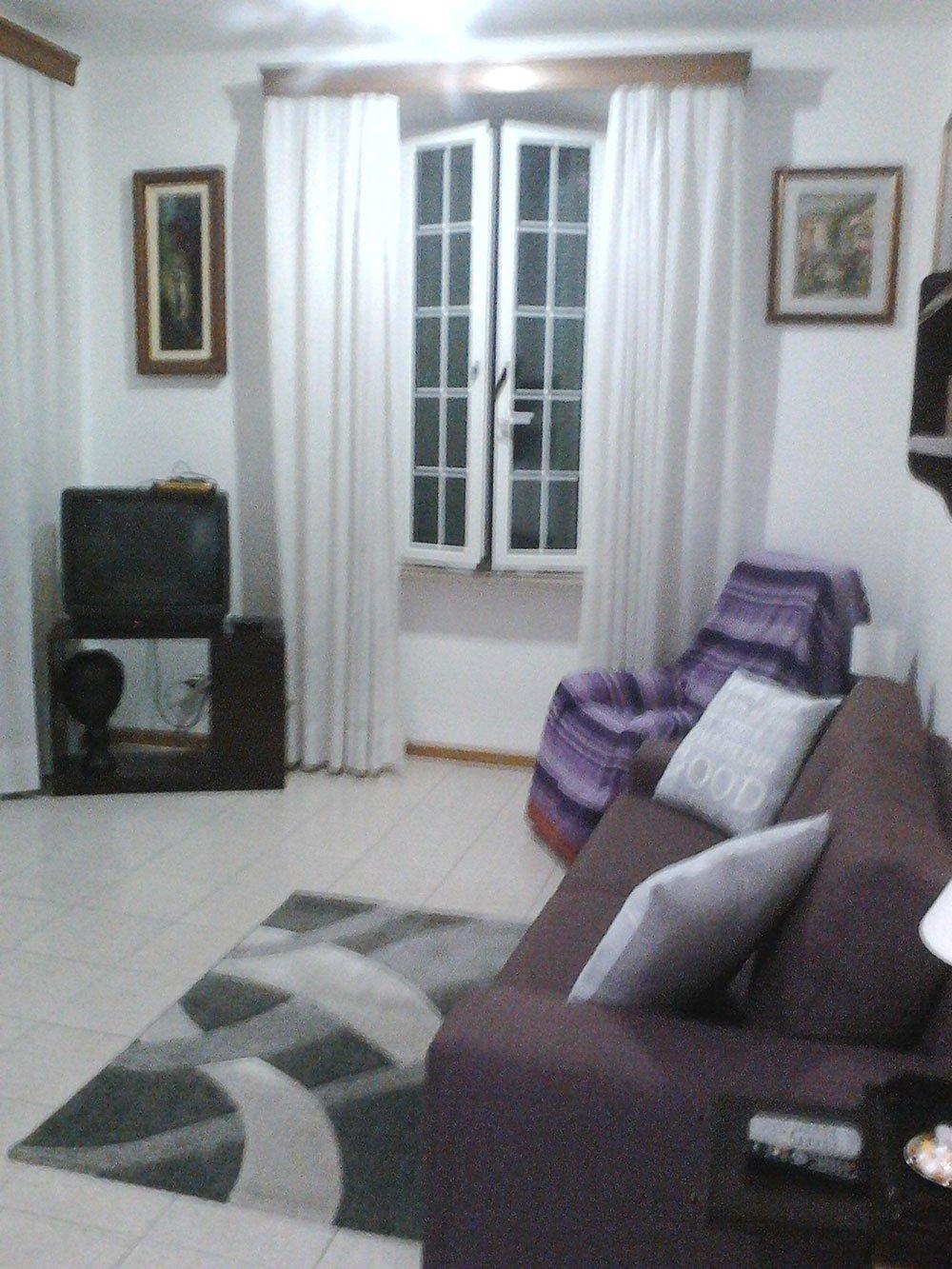 un salotto con un divano marrone con dei cuscini grigi, una poltrona con sopra una coperta viola e fucsia e di fronte un mobile marrone con sopra una tv