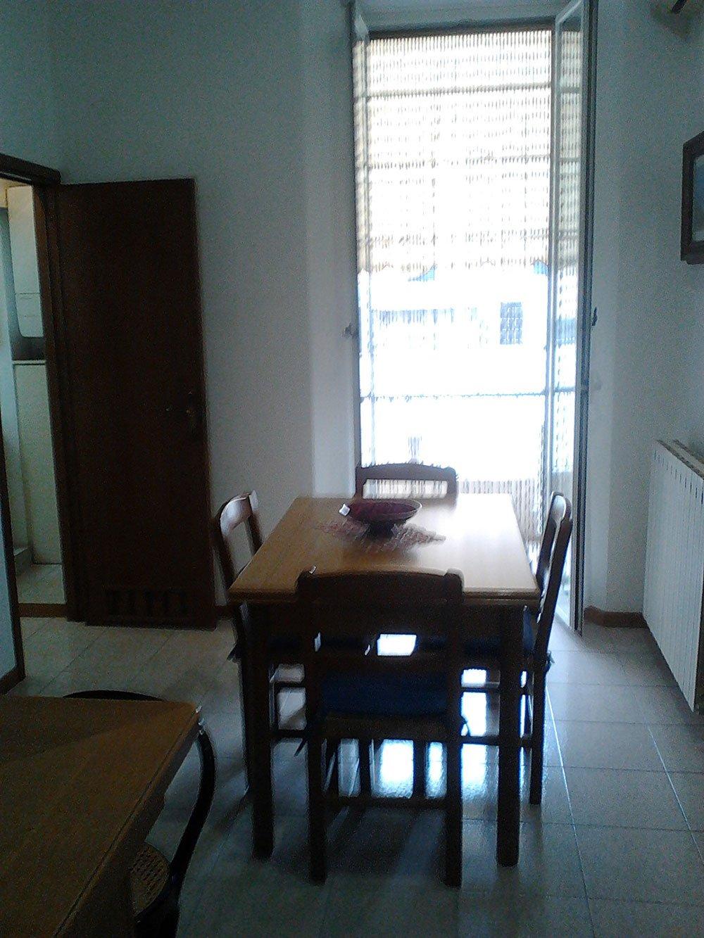 una cucina con un tavolo rettangolare in legno con delle sedie