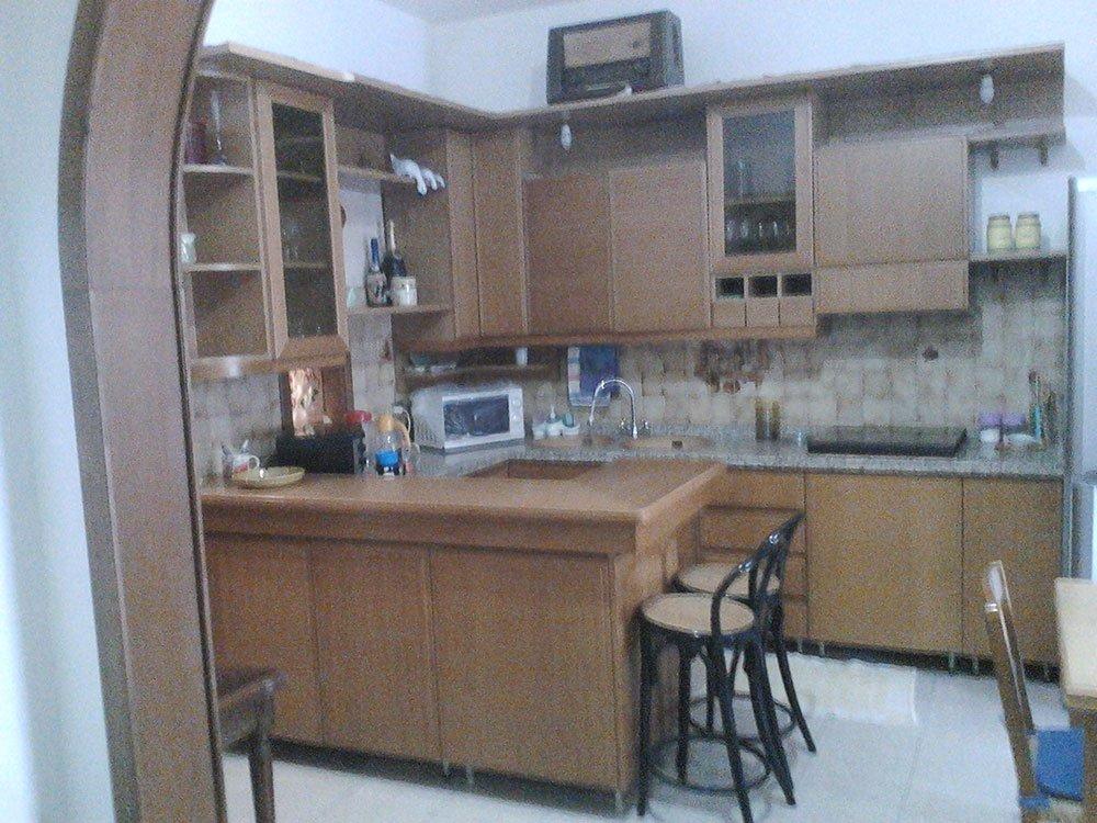 una cucina in legno con penisola e due sgabelli neri