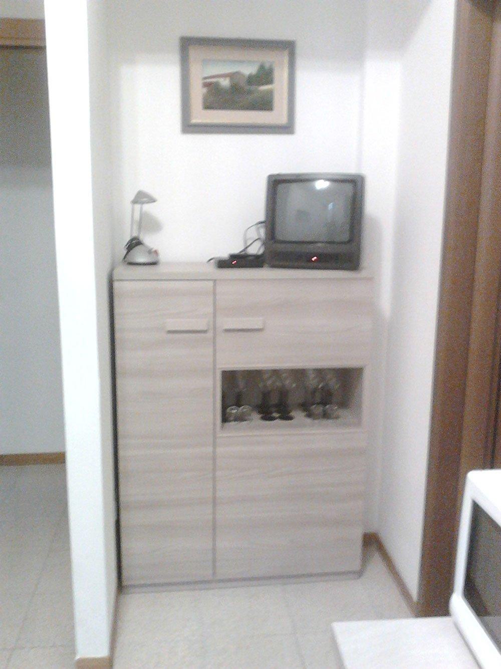 un mobile beige con sopra una lampada e una tv