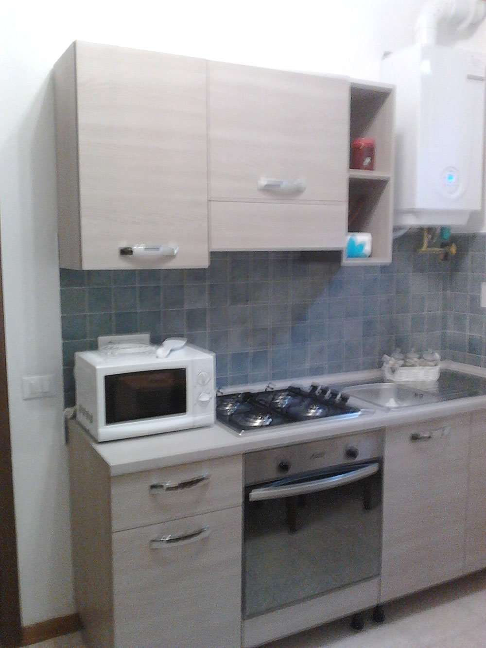 una cucina di color beige con sopra al piano un forno a microonde