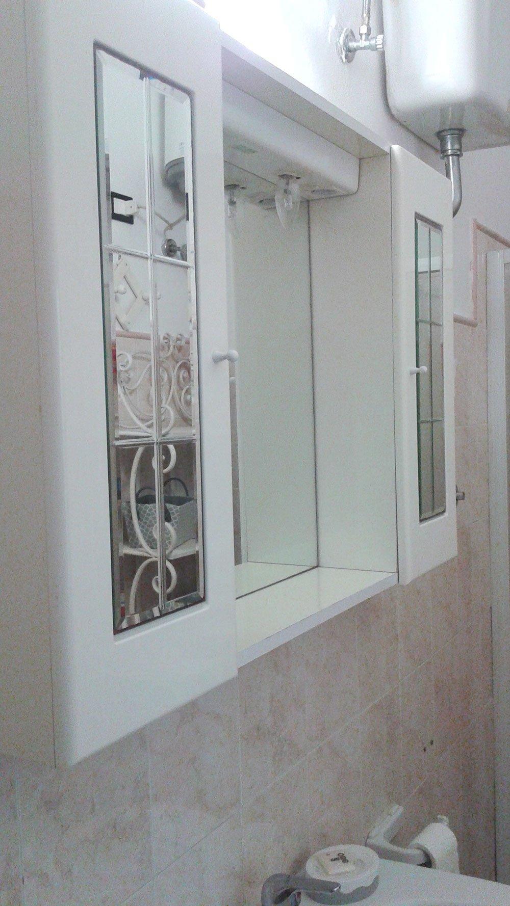 vista di un mobile bianco con due specchi sopra un lavabo in un bagno
