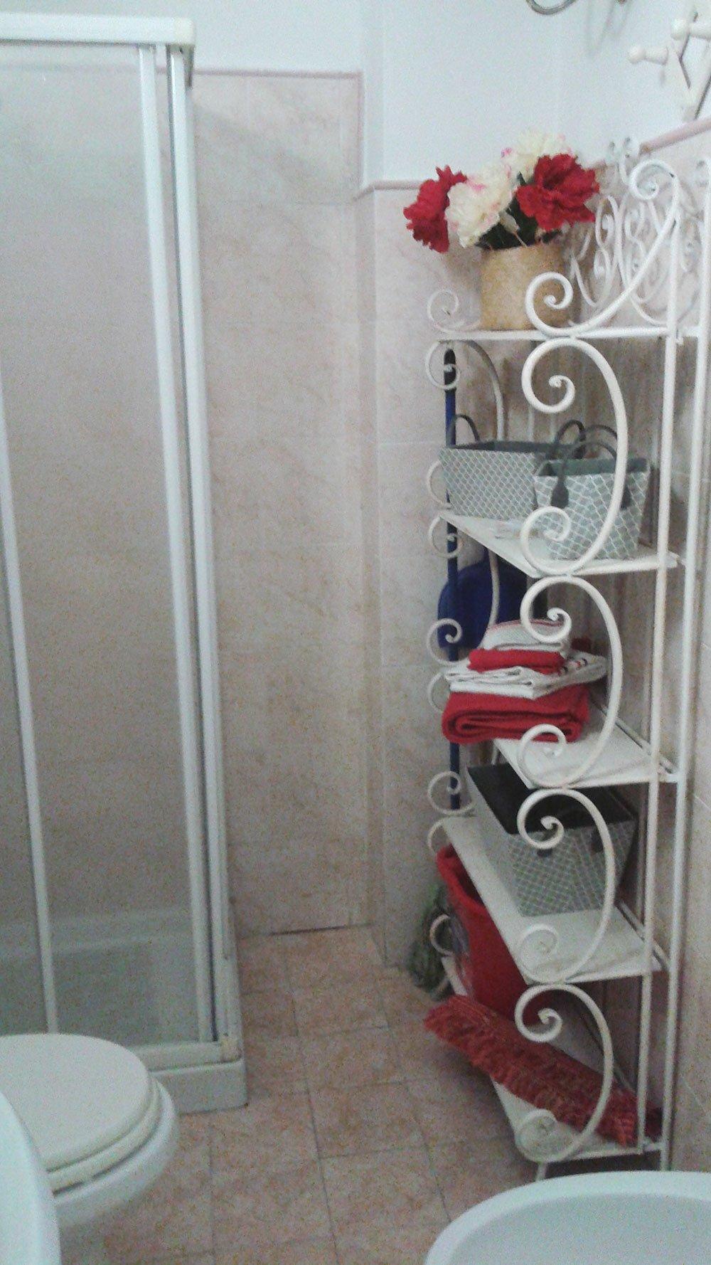 un bagno con sanitari, box doccia e uno scaffale bianco in metallo con asciugamani e vasi con fiori bianchi e rossi