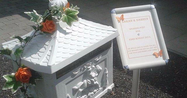 Wedding bost box decorated with peach flowers, and a sign stating