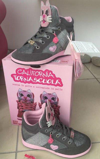 delle scarpe di color grigio e nero con un gatto rosa sulla linguetta