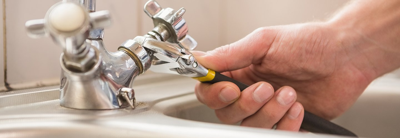 Idraulico che stringe il rubinetto