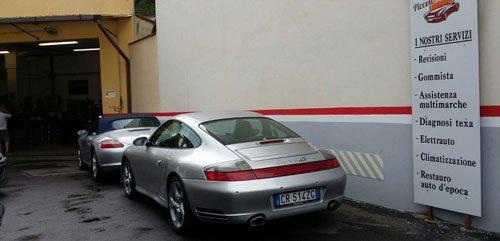 due Porsche grigie parcheggiate fuori dall'officina