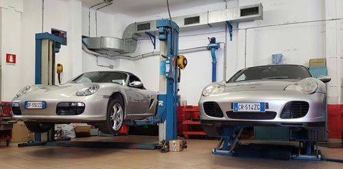 due Porsche grigie su dei ponti elevatori in officina