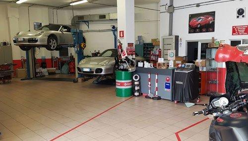 vista dell'interno dell'officina e due Porsche grigie su dei ponti elevatori