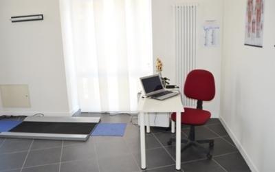 una scrivania bianca con un computer e una sedia rossa