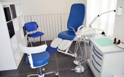 Una poltrona blu e due sedie blu in uno studio di podologia