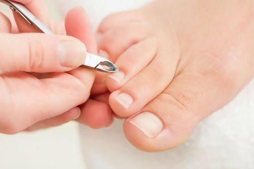 una mano con un tronchesino e delle unghie dei piedi