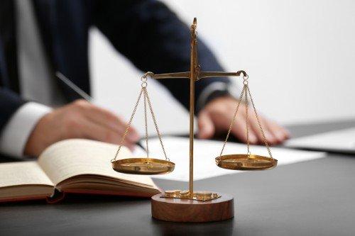 bilancia della giustizia con libro e avvocato sullo sfondo