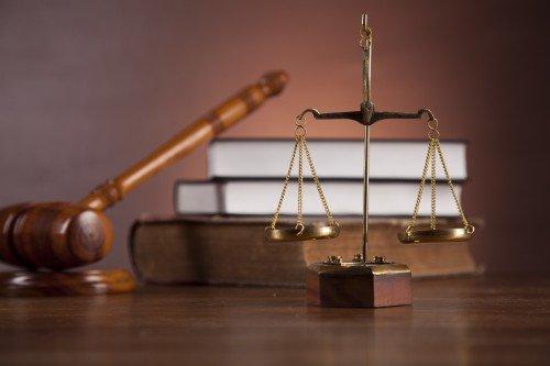 la bilancia della giustizia accanto al martello da giudive e dei libri