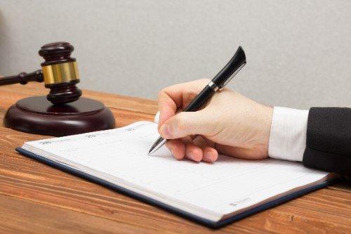 una mano mentre scrive e il martello del giudice