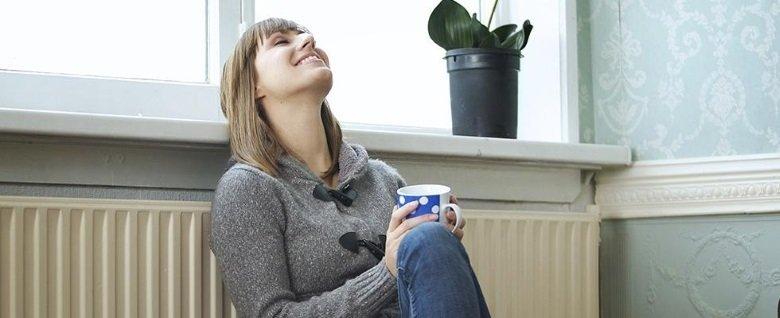 una donna appoggiata a un calorifero con una tazza in mano