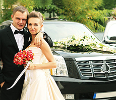 A bride and groom stood together in front of their decorated wedding car