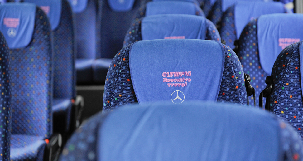 Blue seats with the Olympic Executive Travel logo on them