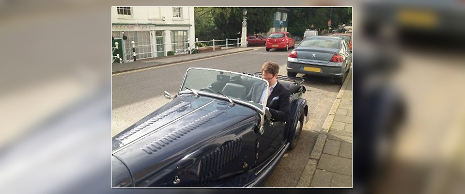 spectacle wearing man in passenger seat of open topped veteran sports car