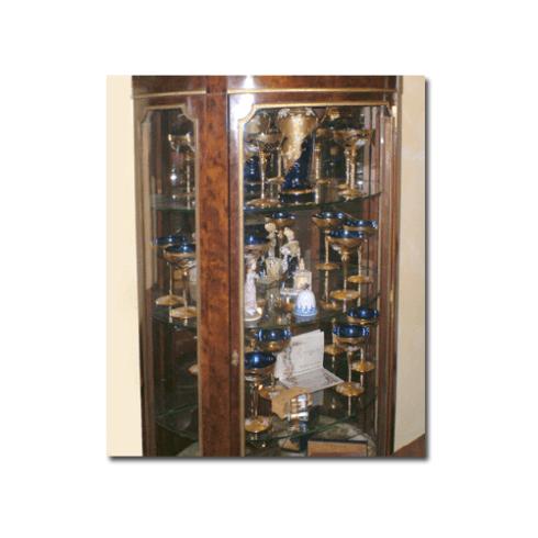 un mobile in legno con dei bicchieri blu e dorati