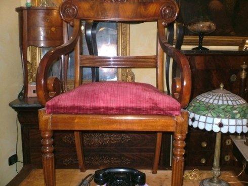 una sedia in legno con un cuscino  di color fucsia