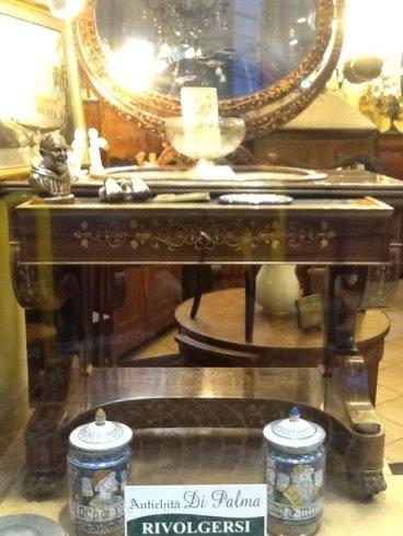 una consolle in legno con uno specchio e due barattoli in ceramica