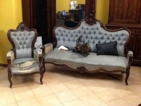 un divano e una poltrona in legno con cuscini di color grigio