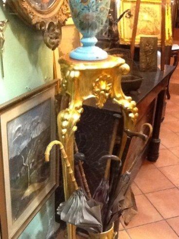 un tavolino dorato con un vaso in ceramica