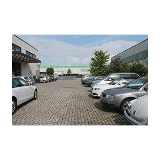 fila di auto parcheggiate fuori una officina