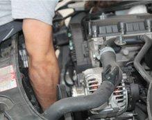 uomo mentre ripara un motore di un auto