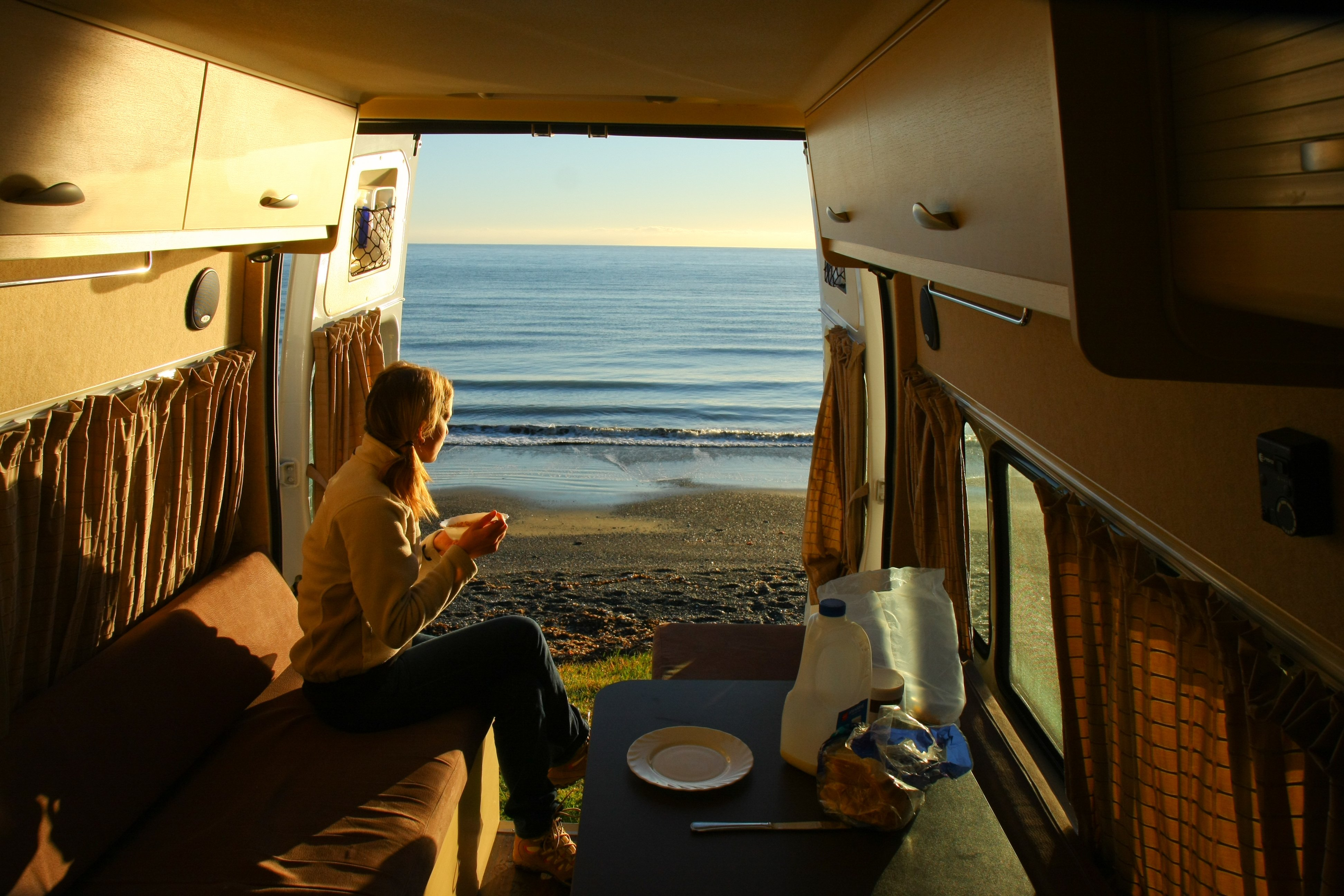A woman looking out to sea from the back of a camper