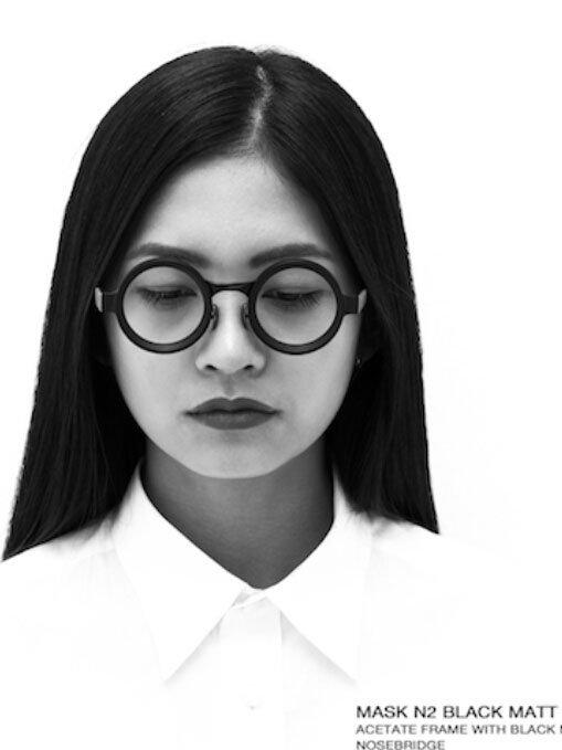 una ragazza asiatica indossa degli occhiali rotondi neri