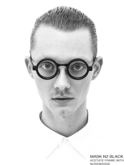 Un ragazzo indossa degli occhiali neri a forma circolare