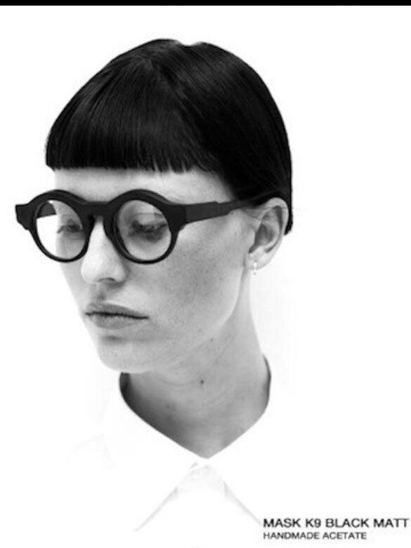 una donna con una frangia e capelli neri indossa degli occhiali circolari con lenti spesse neri