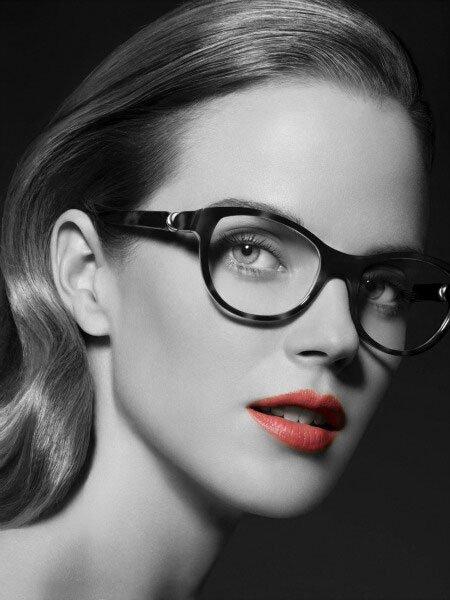 una ragazza con occhi chiari capelli lunghi castani e rossetto indossa degli occhiali di color nero