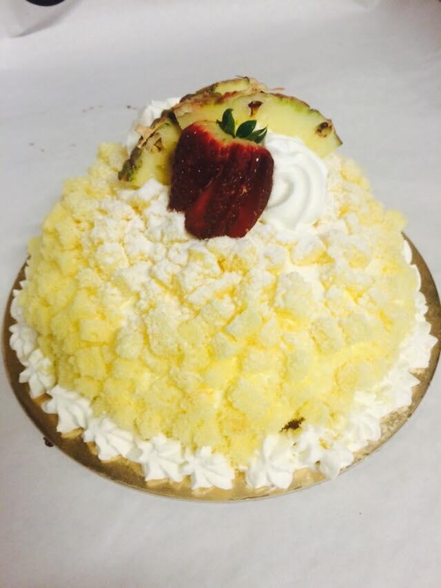 una torta di crema gialla con sopra una fragola