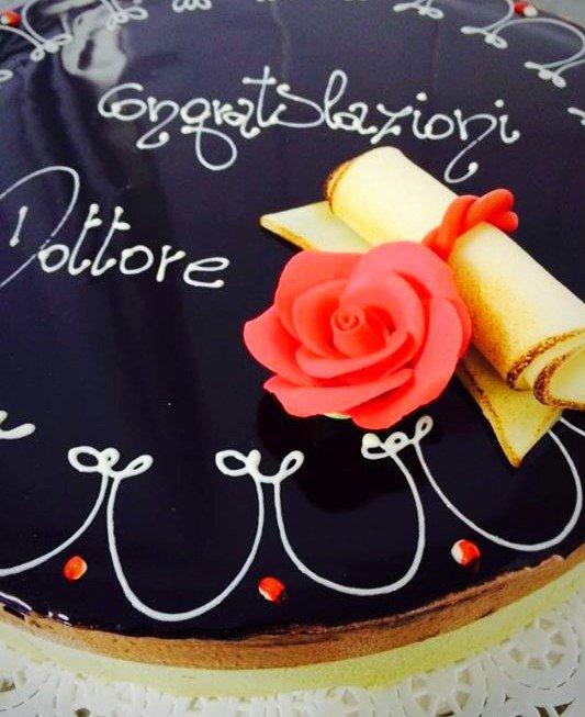 una torta di glassa bianca e rossa con sopra un cappello da laurea