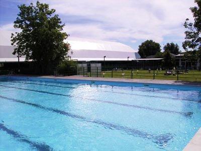 una piscina olimpionica all'aperto e in lontananza una ringhiera nera, un prato e degli alberi