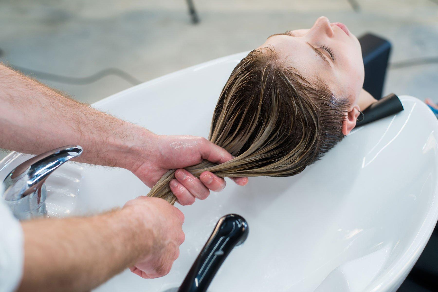 un parrucchiere che lava i capelli di una donna
