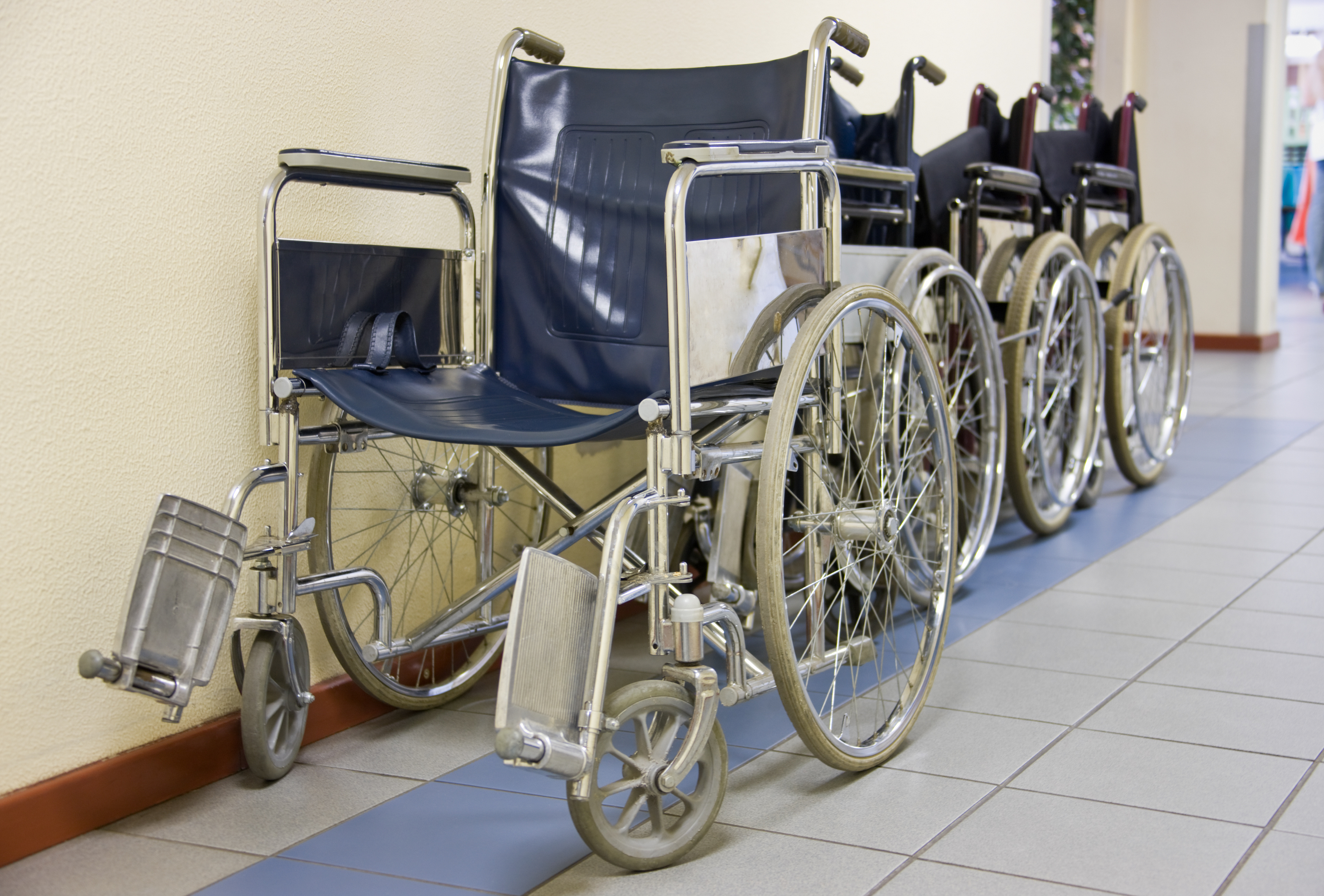 row of wheelchairs in a hospital hallway