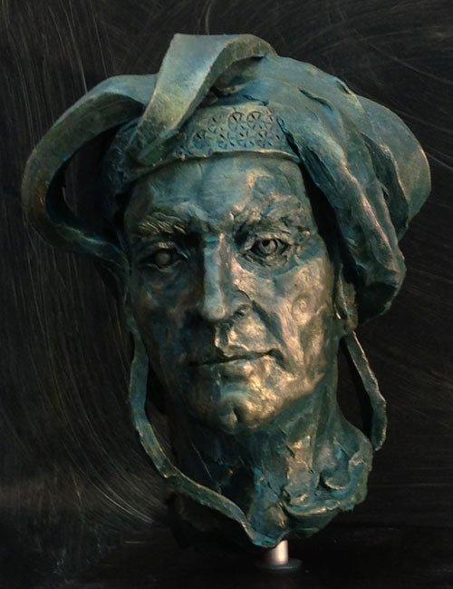 una scultura di un uomo con la barba seduto mentre brandisce una spada e un cane
