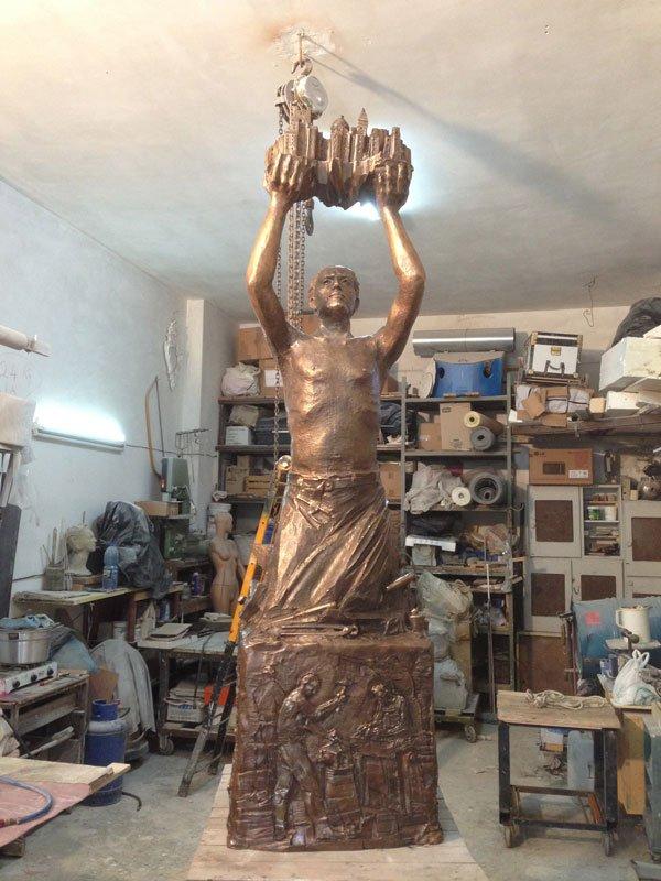 una statua di bronzo di un uomo che solleva una città