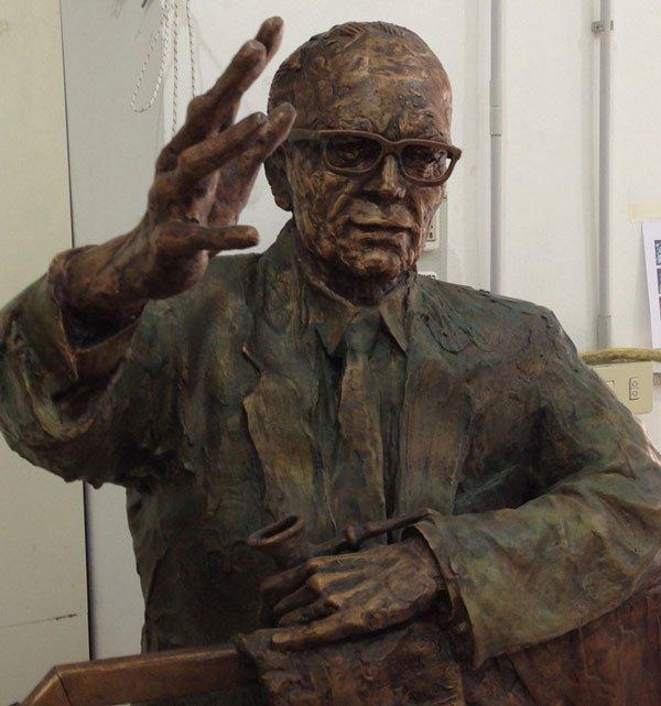una scultura di un uomo pelato con gli occhiali e il braccio alzato