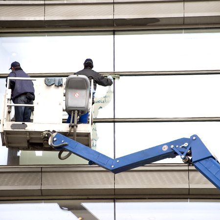 Men cleaning windows using plant equipment to reach upper levels of building