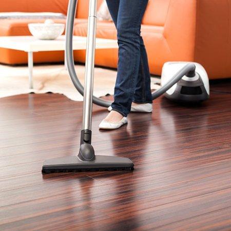 Woman hoovering wooden floor