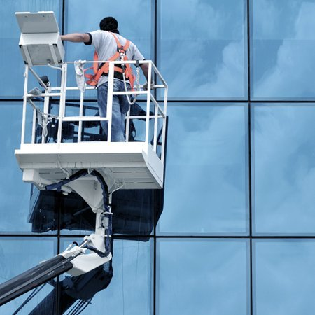 Man on hydraulic platform looking at framework